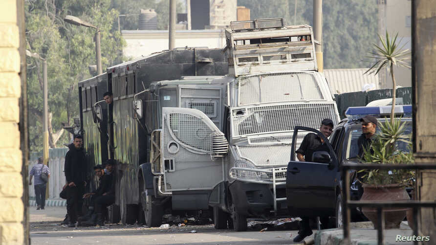 Egyptian police escorts stand by vehicles for general prisoner transport at Tora prison, Cairo, August 22, 2013.