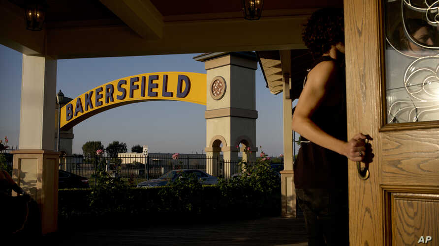 The iconic Bakersfield sign hangs over a street, May 2, 2018, in Bakersfield, Calif. On Wednesday, a gunman killed five people, including his wife, before turning the gun on himself.