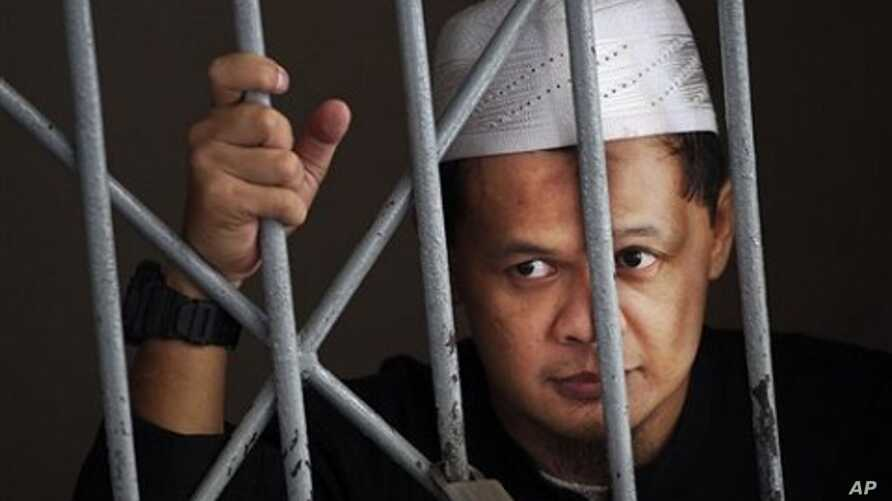 Suspected militant Abdullah Sunata stands behind bars inside a holding cell at a district court in Jakarta, Indonesia (File Photo - March 30, 2011)