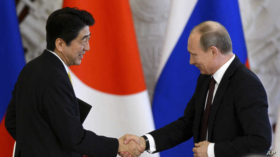 Russia's President Vladimir Putin (R) shakes hands with Japan's Prime Minister Shinzo Abe during a signing ceremony at the Kremlin in Moscow, April 29, 2013.