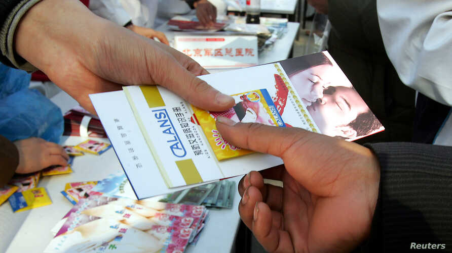 FILE - A Chinese volunteer hands free condom and AIDS prevention brochures during an HIV/AIDS awareness campaign in Beijing.
