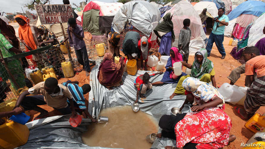 FILE - Internally displaced Somali people gather around a water point at a settlement camp in Hodan district south of capital Mogadishu, Somalia.