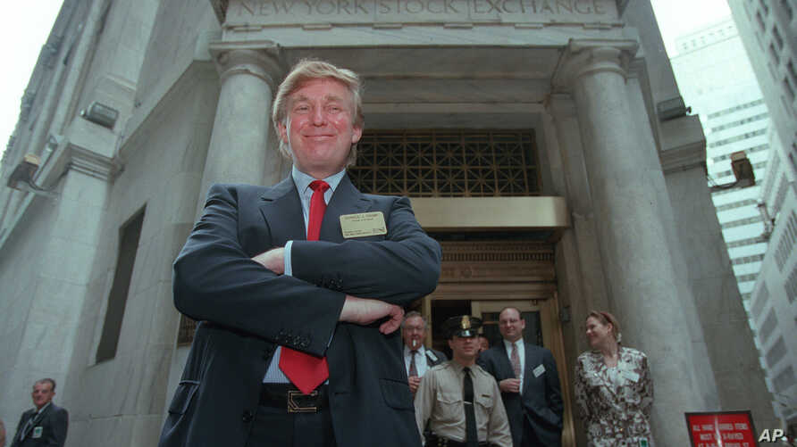 Developer Donald Trump poses for photos outside the New York Stock Exchange after the listing of his stock on Wed., June 7, 1995 in New York.  He took his flagship Trump Plaza Casino public, offering 10 million shares of common stock at an estimated