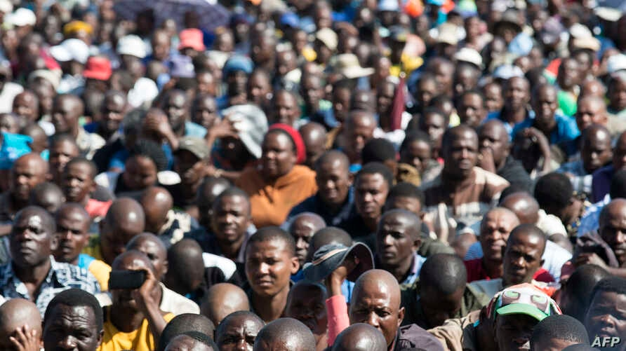 Striking miners gather gathered at the Wonderkop Stadium in Marikana as they wait for Association of Mine workers and construction Union's president Joseph Mathunjwa to address them on May 14, 2014 in Marikana, South Africa.