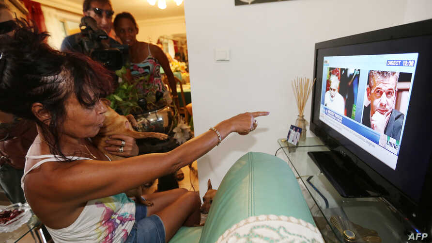 The wife of former French hostage Francis Collomp, Anne-Marie Collomp, watches news on TV, announcing the release of her husband, on November 17, 2013 in Le Port, French overseas island of La Reunion.