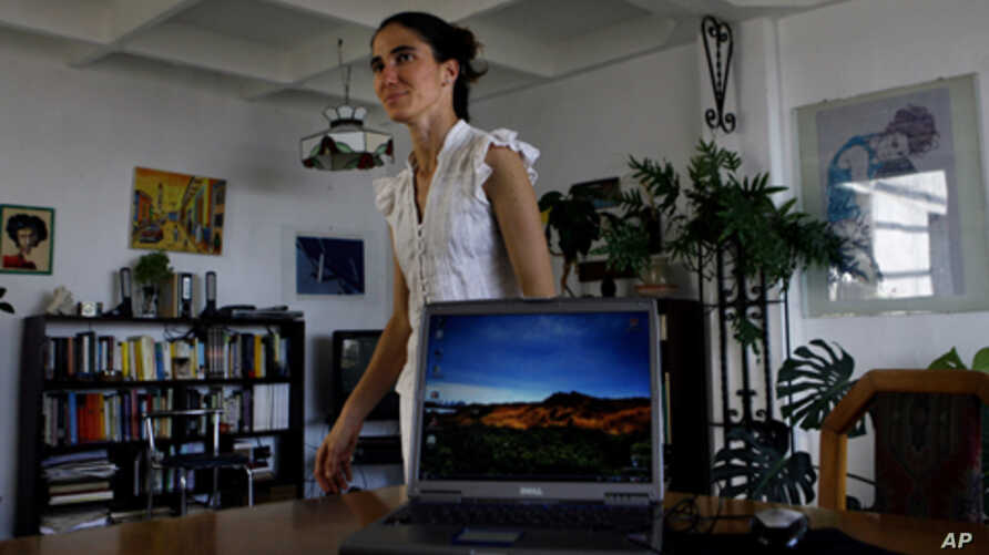 """Yoanis Sanchez, who writes the """"Generation Y"""" blog, walks inside her home in Havana, Friday, April 11, 2008."""
