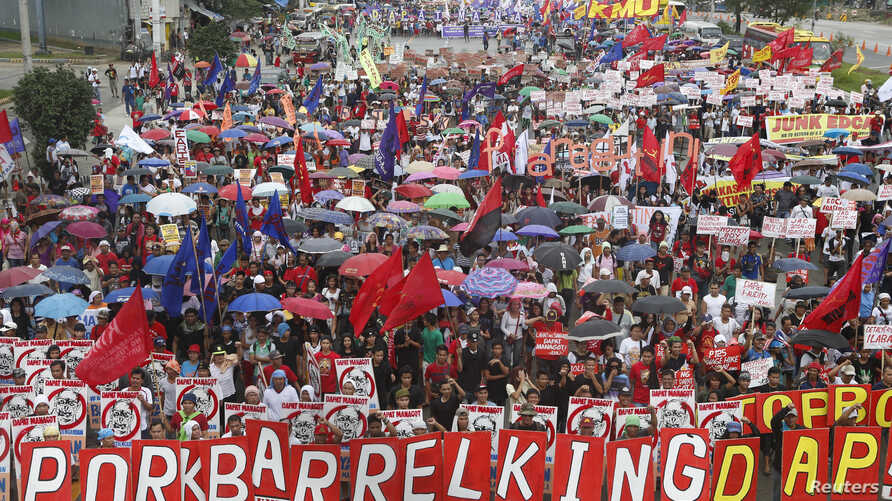 Protesters march to oppose Philippine President Benigno Aquino's fifth State of the Nation Address (SONA) during the joint session of the 16th Congress at the House of Representatives of the Philippines in Quezon city, Metro Manila, July 28, 2014.