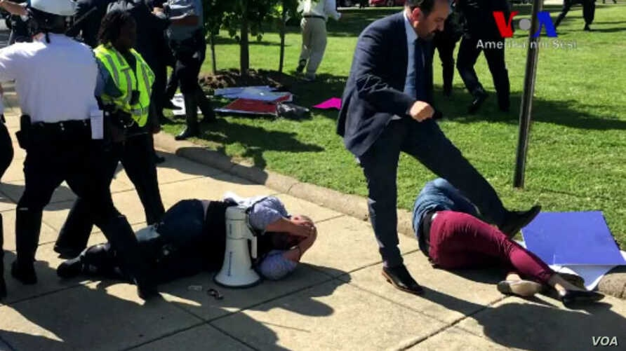 Demonstrators lie on the ground following a brawl with Turkish security personnel near the Turkish ambassador's residence in Washington, May 17, 2017. (screengrab from VOA Turkish video)