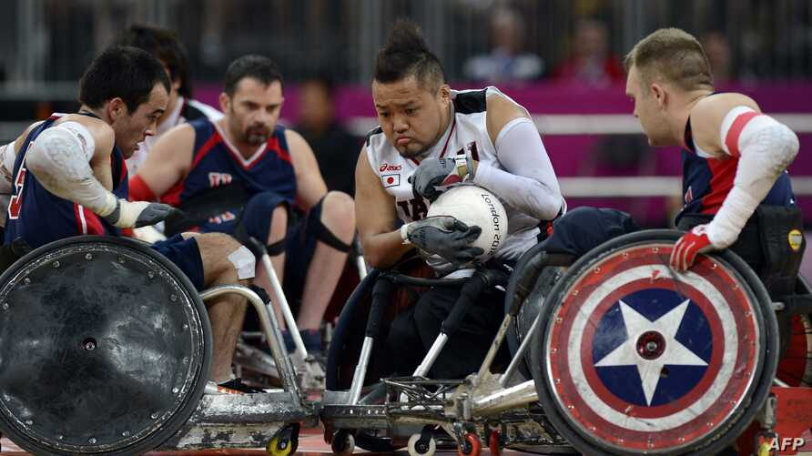 Japan's Shin Nakazato (C) holds onto the ball as Chuck Aoki of the US (L) closes in during the bronze medal Wheelchair Rugby match between USA and Japan at the Basketball Arena during the London 2012 Paralympic Games in the Olympic Park in east Londo