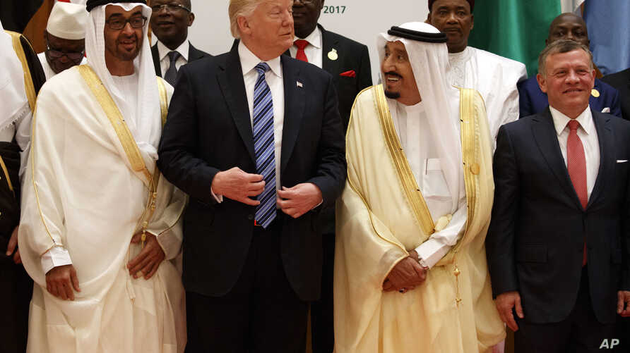 President Donald Trump talks with Saudi King Salman as they pose for photos with leaders at the Arab Islamic American Summit, at the King Abdulaziz Conference Center in Riyadh, Saudi Arabia, May 21, 2017. Jordan's King Abdallah II stands at right.