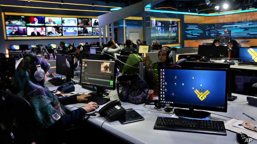 Employees work in the newsroom of Hezbollah's Al-Manar TV station, in the southern suburb of Beirut, Lebanon, Thursday, Dec. 10, 2015.