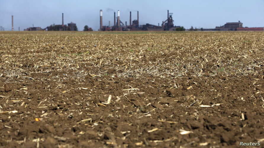 Chimneys from ArcelorMittal steel company are seen behind a dry maize field near Vanderbijlpark outside Johannesburg, South Africa, Oct. 1, 2015. Poor rains are forecast for South Africa's maize belt because of the El Nino weather pattern, expected t