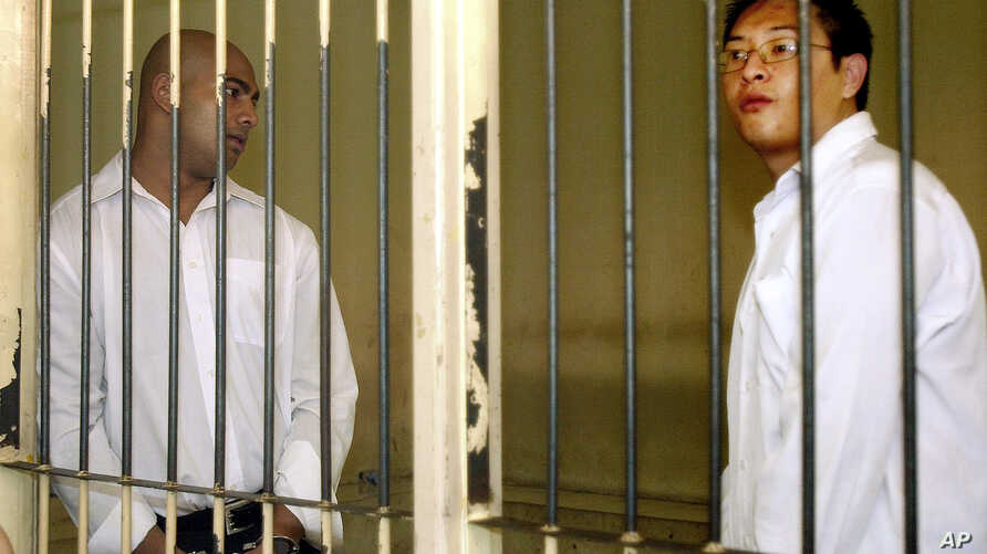 Australian Andrew Chan, right, and, and Myuran Sukumaran, left, stand inside a holding cell after their trial at a court in Denpasar, Bali, Indonesia, Tuesday, Feb. 14, 2006. The two Australians were sentenced to death by firing squad for leading a d