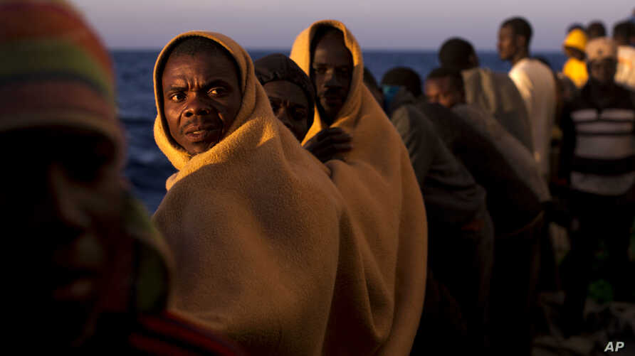 Men stand on the deck of the rescue vessel Golfo Azzurro after being rescued by Spanish NGO Proactiva Open Arms workers on the Mediterranean Sea, June 16, 2017.