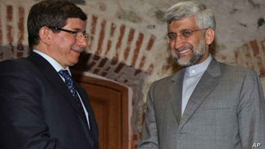 Turkey's Foreign Minister Ahmet Davutoglu (L) and Iran's Chief Nuclear Negotiator Saeed Jalili pose for cameras before their meeting on Iran's nuclear program, in Istanbul, Turkey, April 13, 2012.