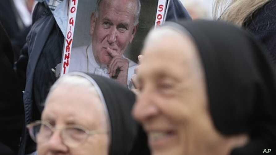 A picture of late Pope John Paul II, is framed by two nuns prior to the start of the Easter mass celebrated by Pope Benedict XVI  in St. Peter's square, at the Vatican, April 24, 2011