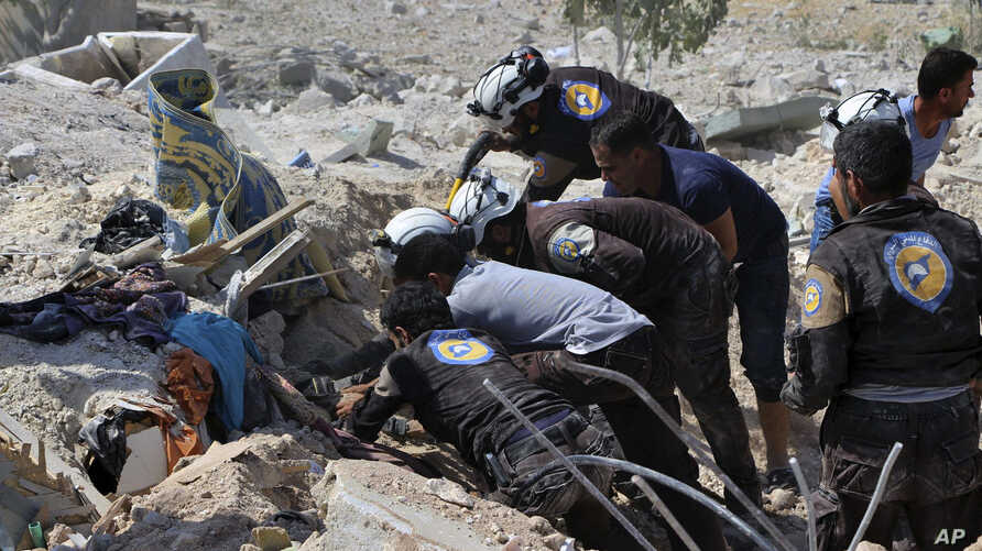 This photo provided by the Syrian Civil Defense White Helmets, which has been authenticated based on its contents and other AP reporting, shows Civil Defense workers searching through the rubble after airstrikes hit in Khan Sheikhoun, in the northern...