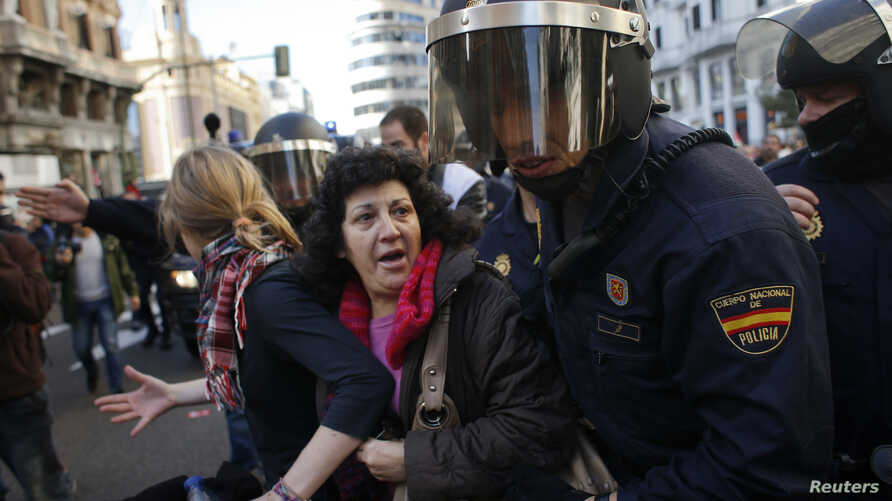 Protesters are pushed away by Spanish police officers during a 24-hour nationwide general strike in central Madrid November 14, 2012.