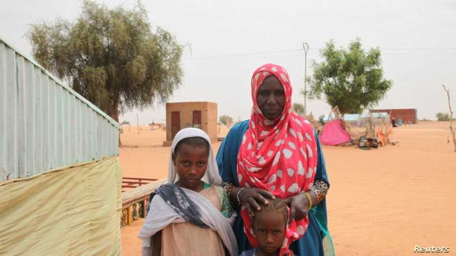 Aminetou Mint Yarg poses with family members in the commune of Dar El Barka, Mauritania, Oct. 20, 2018.