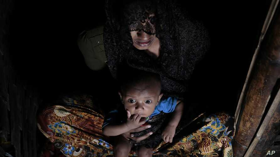 Mohsena Begum, a Rohingya who escaped to Bangladesh from Myanmar, holds her child and sits at the entrance of a room of an unregistered refugee camp in Teknaf, near Cox's Bazar, a southern coastal district south of Dhaka, Bangladesh, Dec. 2, 2016.