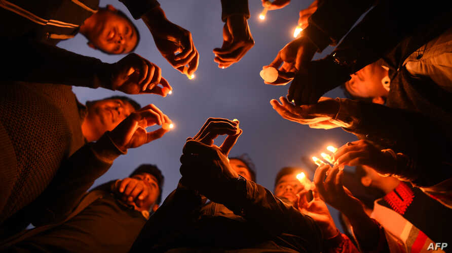 Nepali people take part in a candlelight vigil in honour of the plane crash victims in Kathmandu on March 13, 2018, a day after the deadly crash of a US-Bangla Airlines plane at the international airport.