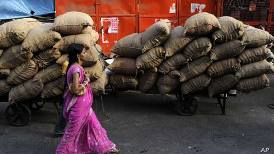 An Indian woman walk past carts loaded with sacks of food items at a wholesale market in New Delhi, India, June 9, 2011.