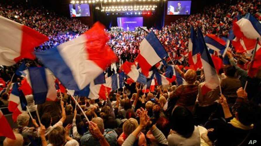 Supporters of France's president and candidate for re-election in 2012, Nicolas Sarkozy, wave French national flags, during a campaign meeting, in Toulon, southern France, May 3, 2012.