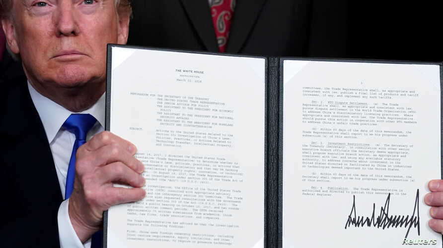 U.S. President Donald Trump holds a signed memorandum on intellectual property tariffs on high-tech goods from China, at the White House in Washington, March 22, 2018.