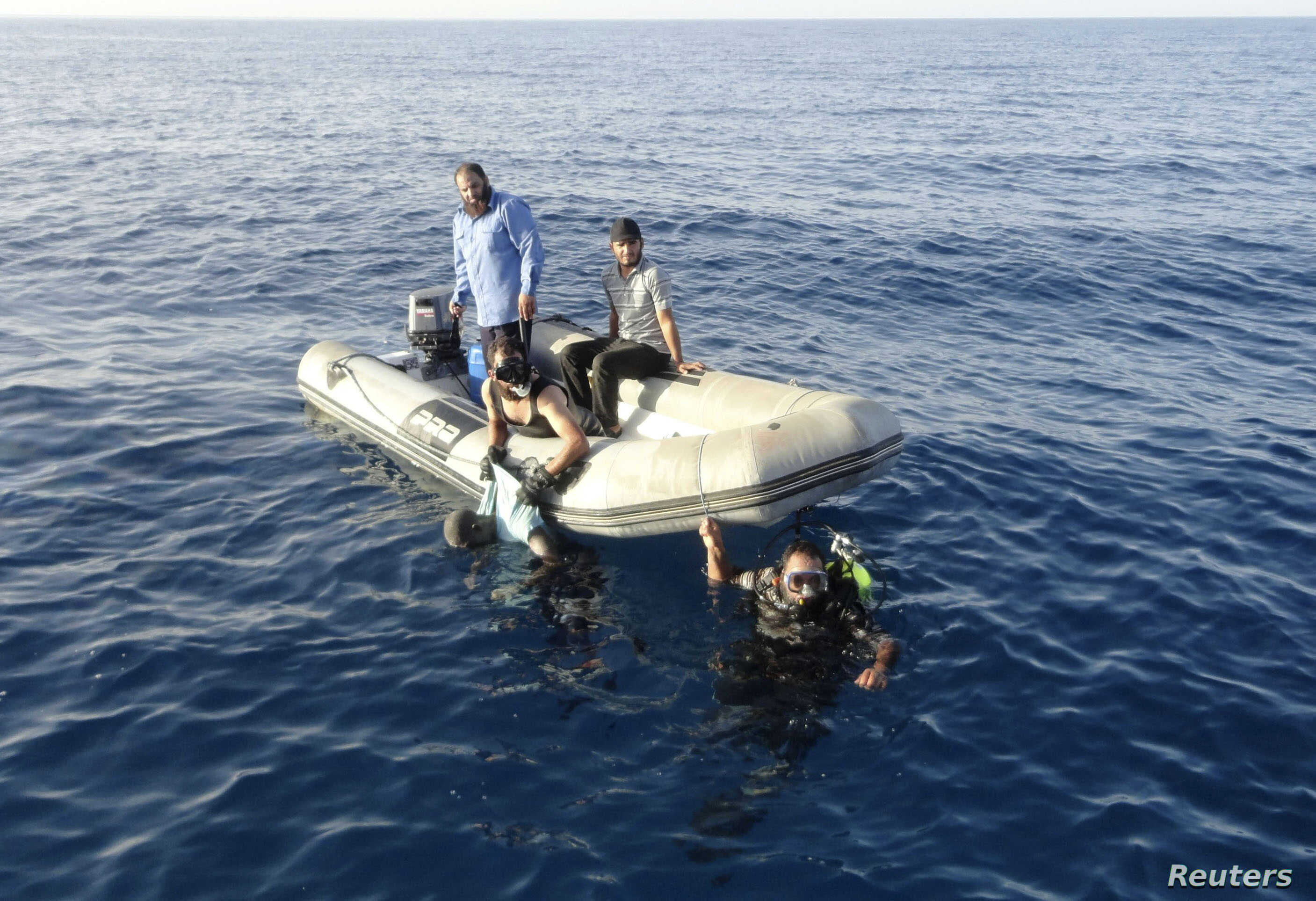 ATTENTION EDITORS - VISUAL COVERAGE OF SCENES OF INJURY OR DEATHMembers of Libya's coast guard recover the body of a migrant who drowned off Tripoli's coast, August 23, 2014. A wooden boat carrying up to 200 migrants has sunk just one kilometre (half