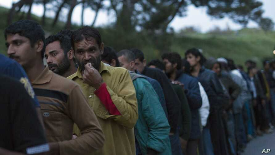 Migrants queue to receive food in a camp set up by volunteers near the port of Mytilini, in the Greek island of Lesbos, Thursday, April 7, 2016.