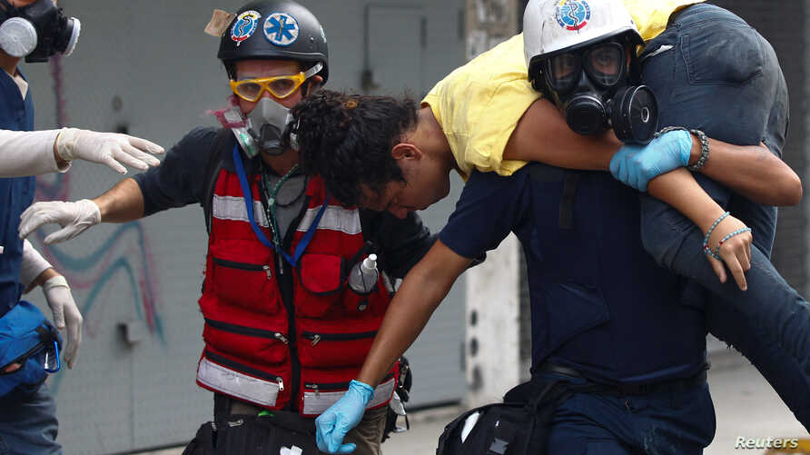 A demonstrator is carried by volunteer members of a primary care response team during a rally against Venezuelan President Nicolas Maduro's government in Caracas, Venezuela, July 1, 2017.