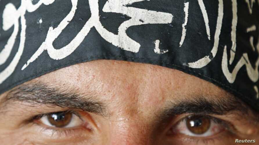 """A Free Syrian Army fighter wears a headband reading the Islamic declaration of faith, """"There is no God but God, and Mohammed is His Messenger"""", in central Aleppo August 9, 2012."""