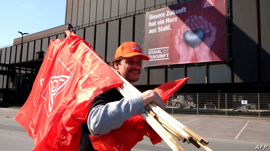 "A steelworker carrying flags by German metalworkers' union IG Metall walks past a banner reading ""Our future has a heart of steel"" during a protest of steelworkers against European policies on April 11, 2016 in Duisburg, western Germany."