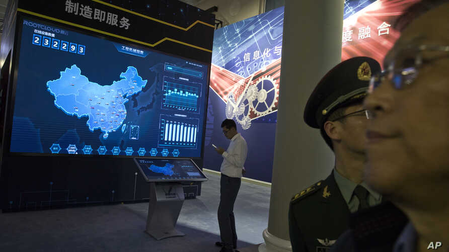 FILE - Visitors look at a display of information technologies at an exhibit highlighting China's achievements under five years of Xi Jinping's leadership at the Beijing Exhibition Hall in Beijing, China, Oct. 17, 2017.