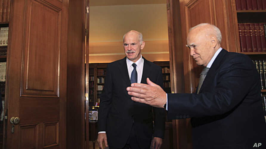 Greece's President Karolos Papoulias (R) welcomes Prime Minister George Papandreou at his office inside the Presidential Palace in Athens, November 5, 2011.
