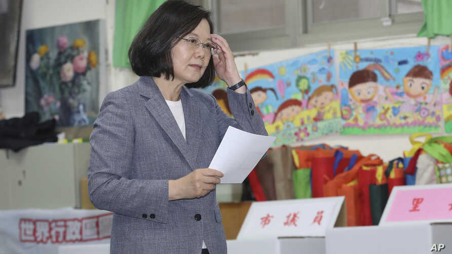 Taiwanese President Tsai Ing-wen waits to cast her ballot, Nov. 24, 2018, in Taipei, Taiwan. Taiwanese began voting in midterm local elections Saturday seen as a referendum on Tsai's independence-leaning administration, amid growing pressure from Chi