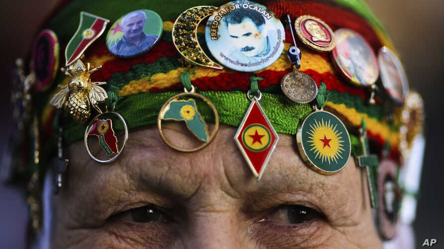 FILE - A woman wears Kurdish symbols and a sticker with a portrait of Abdullah Ocalan, the jailed leader of the rebel Kurdistan Workers' Party, or PKK, as she attends a protest of the visit of Turkish President Recep Tayyip Erdogan in Berlin, Germany