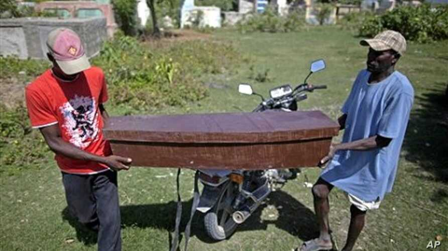 Two men carry the coffin of Frist Fleurant, 10, who died of cholera, before his burial in Rossignol, Haiti,  24 Oct. 2010.