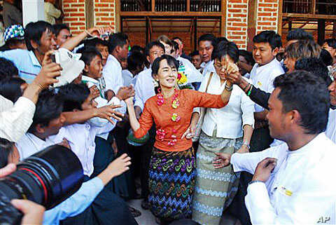 Burma pro-democracy leader Aung San Suu Kyi greets supporters at Kyit Tee village, in Myaing township, central Burma, January 31, 2012.