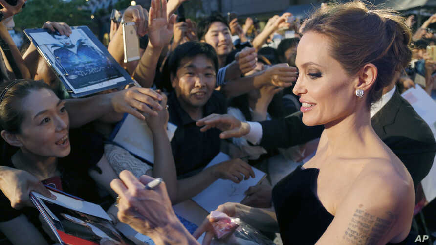 """FILE - Angelina Jolie, soon to direct a film about Kenyan icon Richard Leakey, greets fans at the Tokyo premiere of """"Maleficent,"""" June 23, 2014."""