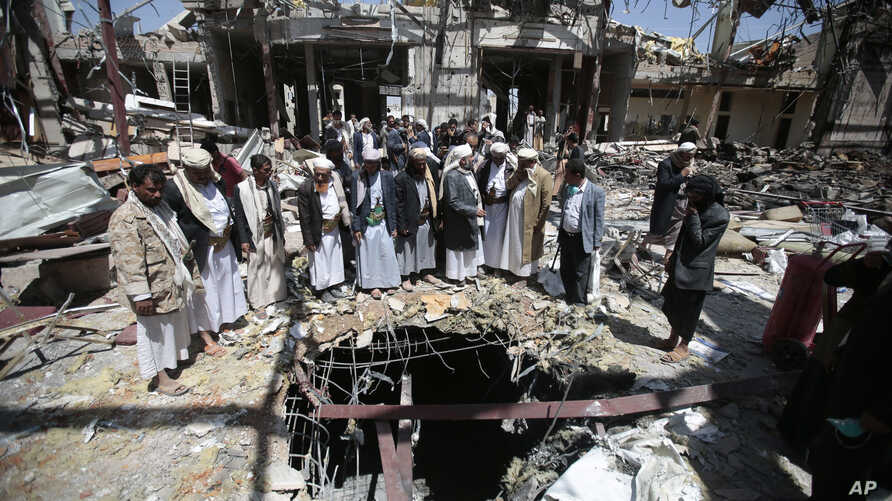 FILE- In this Thursday, Oct. 13, 2016 file photo, members of the Higher Council for Civilian Community Organization inspect a destroyed funeral hall as they protest against a deadly Saudi-led airstrike on a funeral hall six days ago, in Sanaa, Yemen....
