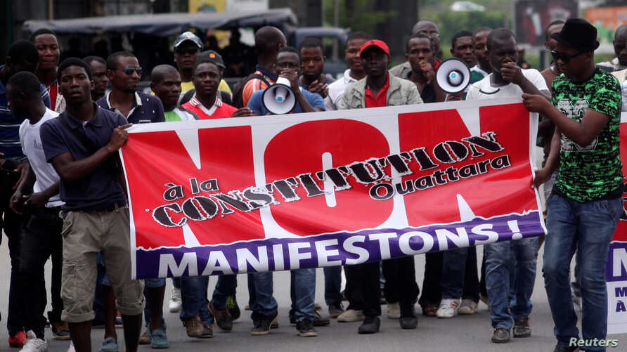 """Members and supporters of the Ivorian Popular Front (FPI) party protest against President Alassane Ouattara's new constitution, in Abidjan, Ivory Coast, Oct. 8, 2016. The banner reads, """"No to Ouattara constitution."""""""