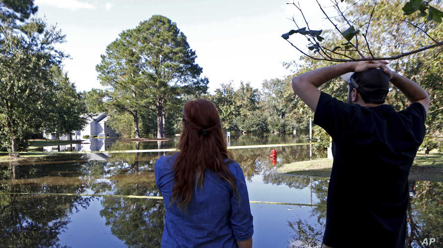 Hurricane Matthew-North Carolina: Caitlyn Cain, left, and friend Sidney Daniels inspect flooding associated with Hurricane Matthew near Cain's old home, Wednesday, Oct. 12, 2016, in Greenville, N.C.