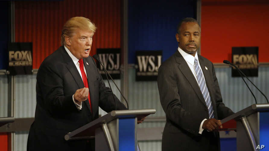 Donald Trump speaks as Ben Carson listens during the Republican presidential debate at the Milwaukee Theatre, Nov. 11, 2015, in Milwaukee