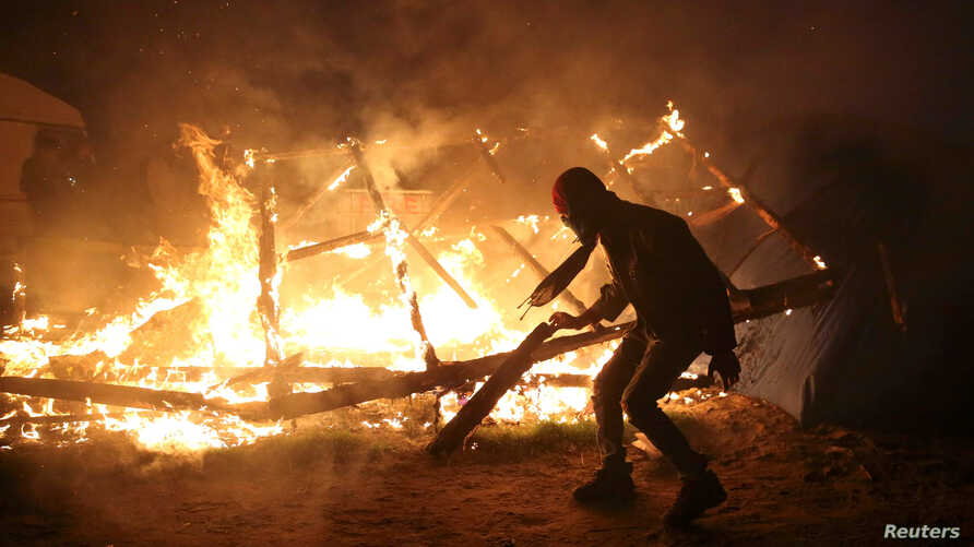 """A migrant is seen in silhouette near flames from a burning makeshift shelter on the second day of the evacuation of migrants and their transfer to reception centers in France, as part of the dismantlement of the camp called the """"Jungle"""" in Calais, Fr"""