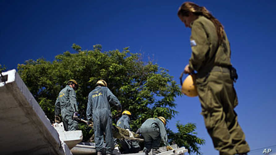 Israeli soldiers from the Home Front Command take part in a drill simulating a building collapse following a mock rocket attack at Zikim army base, near the southern city of Ashkelon, June 19, 2011