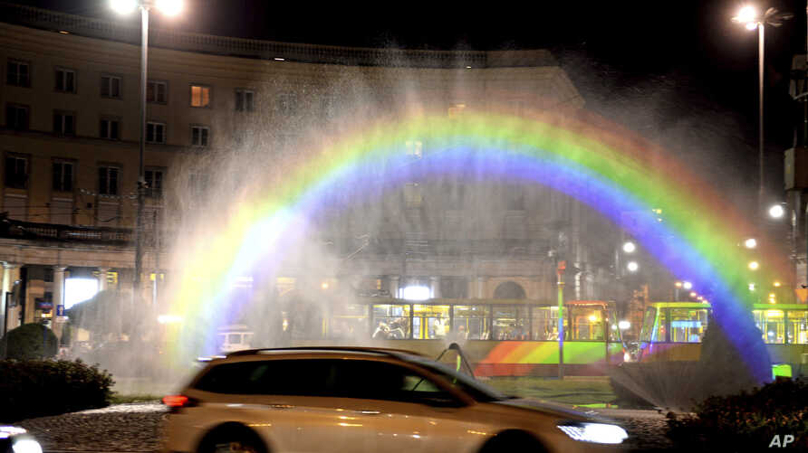 Cars drive past a light-and-water rainbow installation on the night before a gay pride parade, in downtown Warsaw, Poland, June 8, 2018.