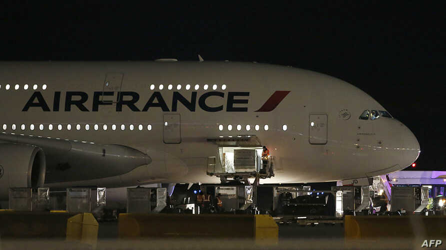 FILE - Workers load cargo on an Air France Airbus 380, Flight 65,  on the runway at Salt Lake City International Airport after being inspected by the FBI on Nov. 17, 2015 in Salt Lake City, Utah.