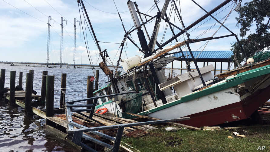 A shrimp boat is sunk at its mooring along the Pascagoula River in Moss Point, Mississippi, Oct. 8, 2017, after Hurricane Nate made landfall on Mississippi's Gulf Coast.