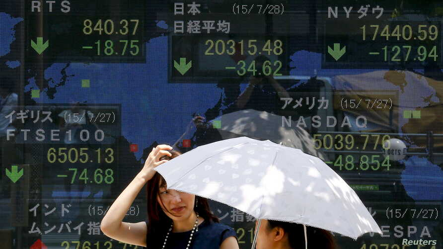 FILE - Women stand in front of a board showing market indices in Tokyo July 28, 2015.